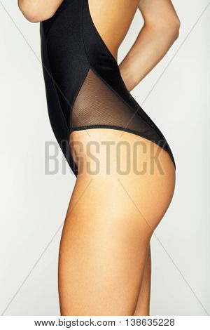 Woman body in black swimsuit. Isolated on white background