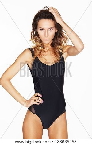 Stylish sexy girl in a black swimsuit isolated on a white background