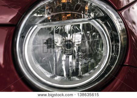 Red car round headlights outdoor close up