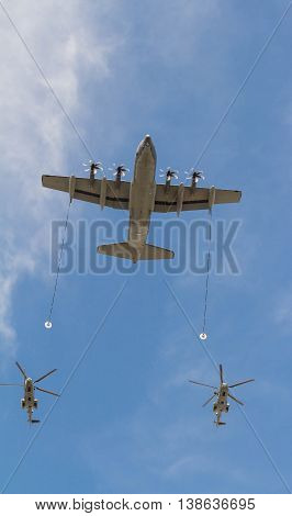 Paris France-July 14 2016 : The aitcraft tanker and two helicopters fly over Paris during Bastille Day military parade on Champs Elysees avenue .