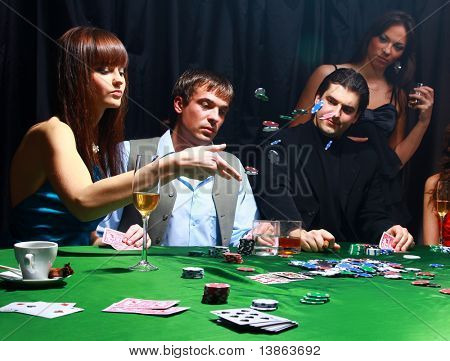 Young women throwing chips on the table while playing cards