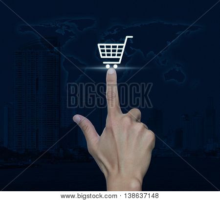 Hand pressing shopping cart icon over map and city tower Shop online concept Elements of this image furnished by NASA