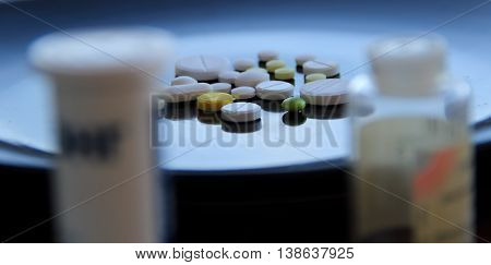 Scattered tablets on glossy surface behind plastic bottles of pills