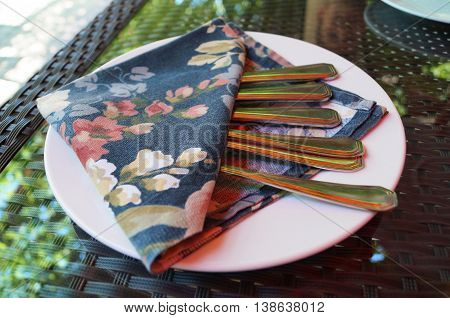 Forks and knives wrapped in a colorful napkin on a white plate