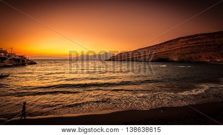Sunset at Matala beach on Crete island, Greece. There is a girl walking on the beach. The colors in the sky are very beautiful, yellow, orange and red.