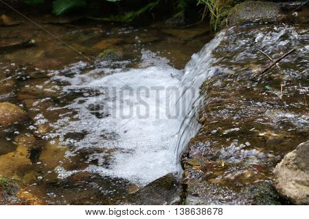 A small waterfall with white foam from the river , which flows over the rocks
