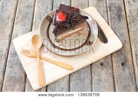 close up chocolate layer cake with cherries topping on wood table