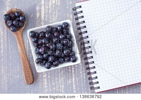 Spoon, Bowl With Blueberries And Blank Notebook