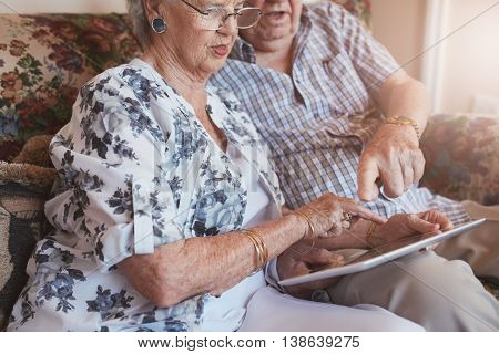 Retired Couple At Home Using Touch Screen Computer
