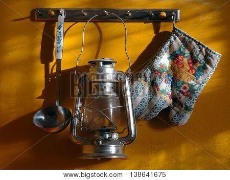 kitchen utensils and a kerosene lamp hanging on a yellow wall