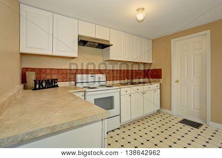 White Kitchen Room With Tile Floor And Brown Back Splash Tile.