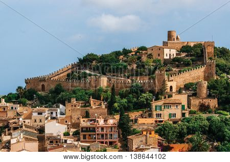 Capdepera castle on green hill in Mallorca island Spain. Beautiful landscape with medieval architecture in Majorca