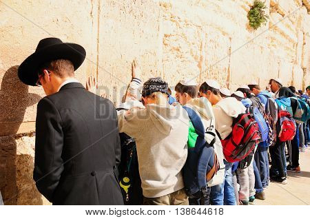 JERUSALEM, ISRAEL - MARCH 22:   Religious orthodox jew and jewish children pray on March 22, 2015 at the Western wall  in Old Jerusalem city.