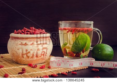 Tibetan goji berries in ceramic bowl and cup of tea with measuring tape and lime on wooden background. Wolfberry for a healthy diet. Alternative medicine. Rejuvenation. Slimming. Selective Focus.