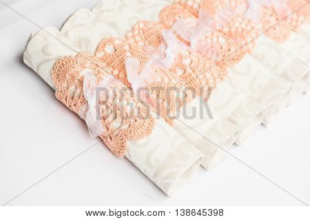 White napkins in pink napkin vintage ring sitting on a plate. Linen textile background. Shallow DOF.