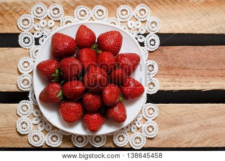 Ripe strawberries on a plate on wooden plates a top view space for text