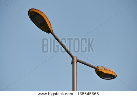 Closeup of an electric pylon on the street with two bulbs