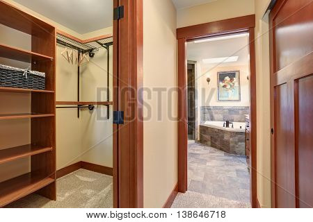 Empty Dressing Room With Carpet Floor And View Of Master  Bathroom.