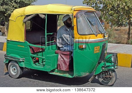 New Delhi, India - february 21, 2006: Tuk- tuk in the livery of the city of New Delhi, circulating in the city