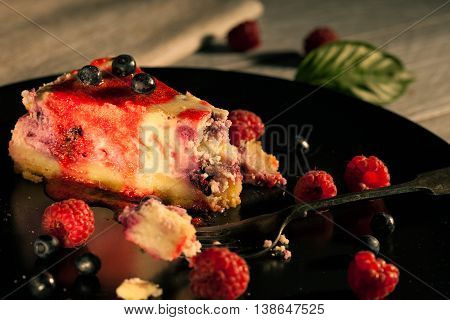 Cheesecake with blueberries and raspberries on a black plate
