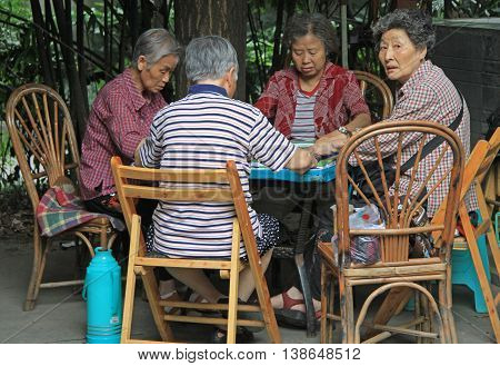 Chinese People Are Playing Domino Outdoor In Park Of Chengdu