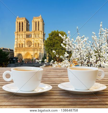 two cups of coffee in Paris with view of Notre Dam cathedral