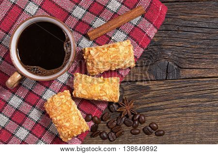 Coffee cup and puff biscuits with cheese on wooden table with tablecloth top view