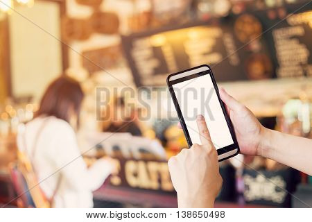 Hand using smartphone and Blurred people in coffee shop with vintage tone.