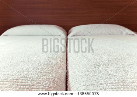 Fragment of an interior of a bedroom. Tucked bed closeup. White terry cover