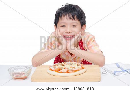 Asian boy cooking pizza on table over white background
