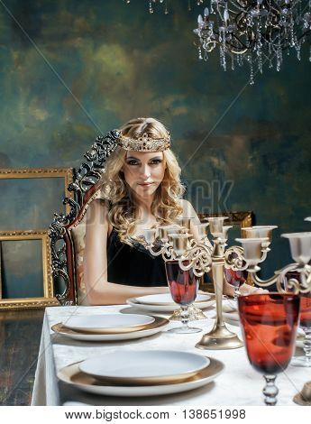 young blond woman wearing crown in fairy luxury interior with empty antique frames total wealth close up