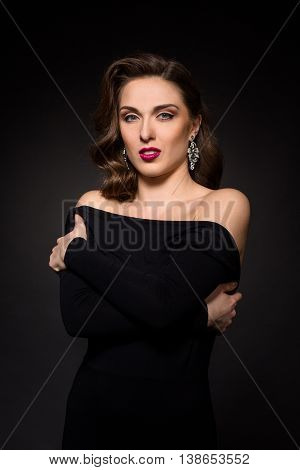 Portrait of beautiful model lady in black dress posing in studio. Professional model woman posing with her arms crossed or folded over black background.
