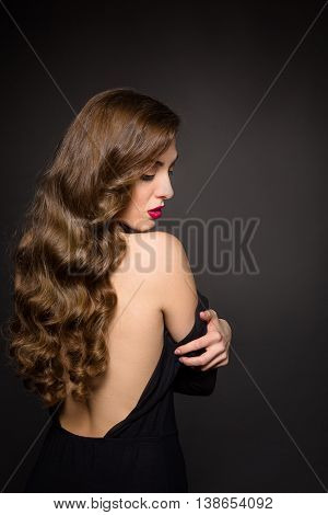 Portrait of beautiful model lady with long brown hair posing over black background. Pretty woman with red lips showing her gorgeous back in studio. Skincare concept.