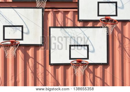 the abstract composition several of basketball baskets with rectangular boards is located on a wall of iron containers