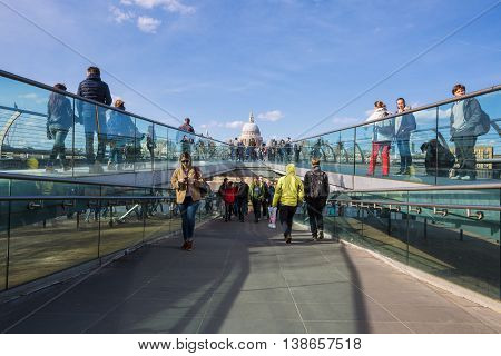 LONDON - APRIL 11: People walk across Millennium Bridge. Background is St Paul's cathedral in London England. Bridge was opened 10 June 2000. Taken on April 11 2015.