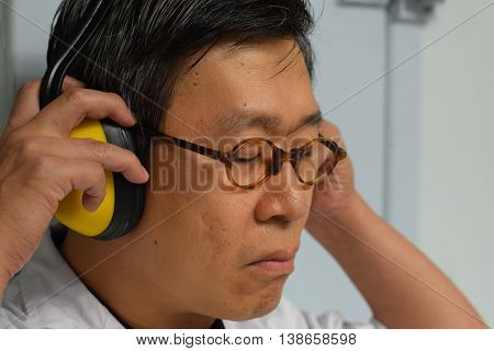 An acoustic engineer listening to the audio through his headset
