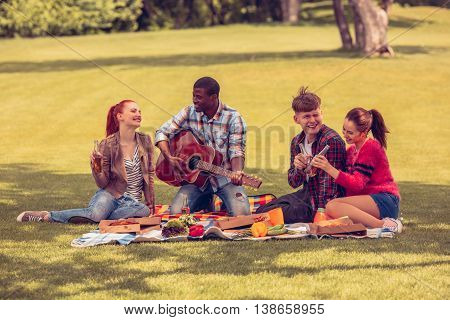 Best friends resting and relaxing picnic in park. People enjoying listening to guitar. Happy men and women drinking cocktails and singing songs.