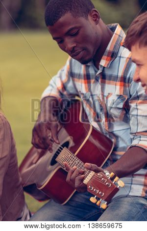 Closeup portrait of Afro-American man playing guitar while resting and relaxing with his best friends on picnic in park.