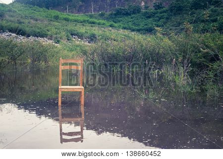 empty wooden chair in water with reflection