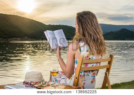 Woman Reading A Book By The Lake