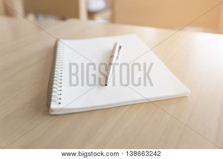Ballpoint Pen And Notebook On Wooden Desk