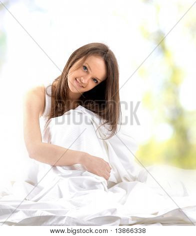Portrait of smiling blonde woman on the bed.