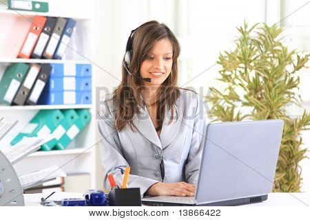 Portrait of a beautiful business woman working at her desk with a headset and laptop