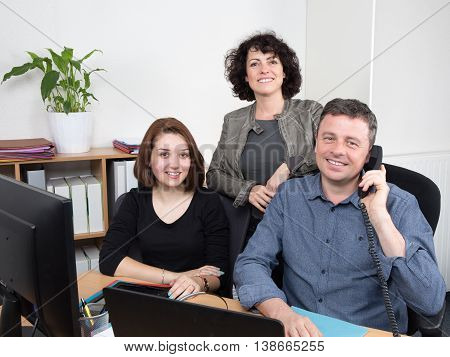Successful businessteam of three sitting in the office and planning work
