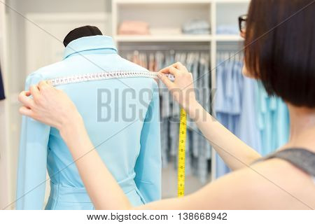 Smart female tailor is measuring dress on mannequin with tape. Woman is standing and looking at clothing with concentration