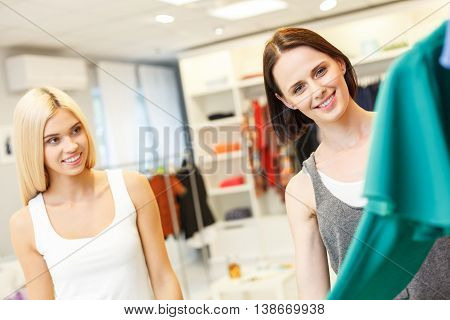 Young saleswoman is showing fashionable dress to customer. She is holding clothing and smiling. Blond woman is standing with joy in boutique