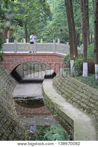Chengdu China - June 16 2015: man is talking by phone on bridge in park of Chengdu China