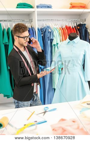 Cheerful young tailor is working in atelier. He is talking on mobile phone and smiling. Man is standing and touching dress on mannequin