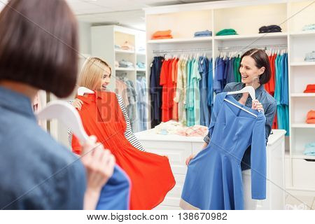 Joyful two women are holding up dresses and looking at mirror in shop. They are standing and laughing