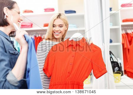 This dress suits you well. Cheerful girls are trying on clothing in boutique. They are looking at each other with satisfaction and smiling. Friends are standing near mirror